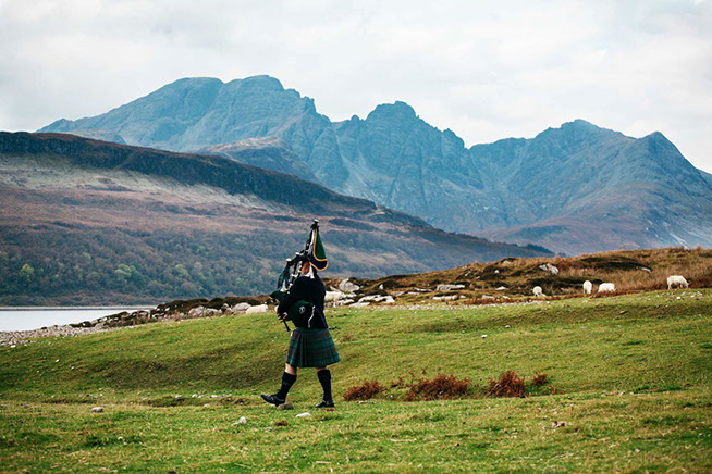 Alistair Ally K Macpherson playing beside the Cuillin Mountain Range on the Isle of Skye in Scotland