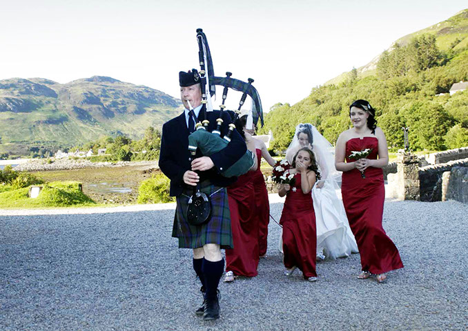 The Skye Piper playing at a wedding at Eiilan Donan Caste near the Isle of Skye